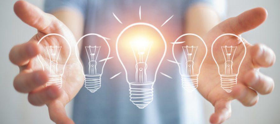 Businessman on blurred background holding a sketch lightbulb